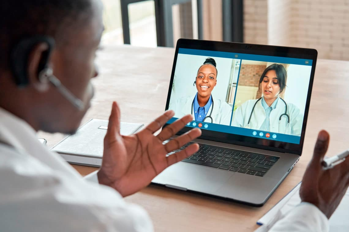 Male doctor gesturing on a video call with two woman doctors.